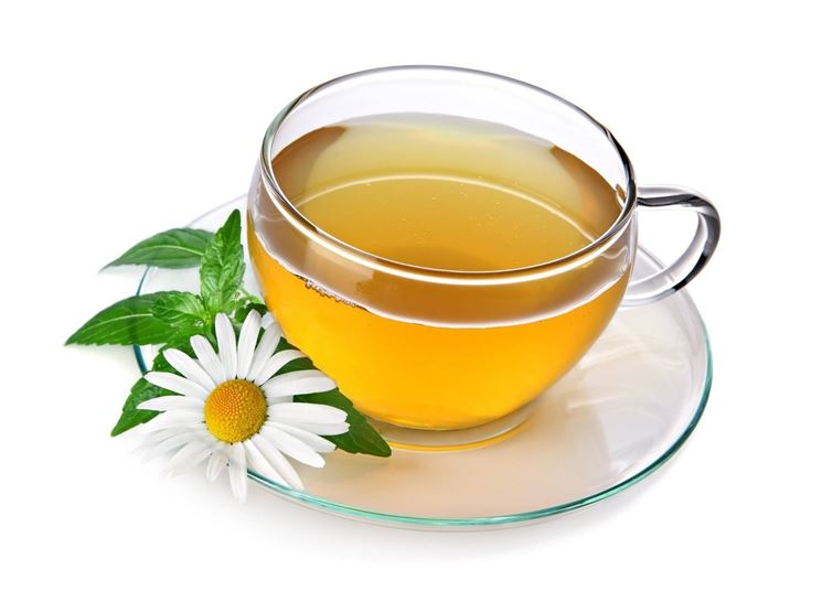 La foto ritrae una tazza di camomilla con il rispettivo fiore all'interno.