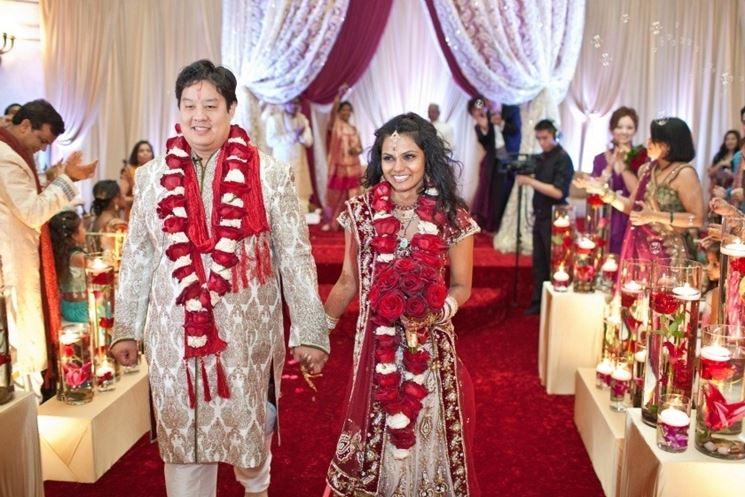 Sposi indiani indossano la tradizionale ghirlanda di rose rosse