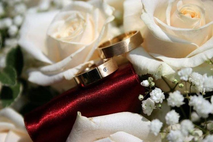 Immagine delle fedi su un bouquet di rose bianche.