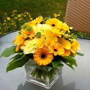 Una solare composizione di fiori gialli tra cui gerbrere e calle