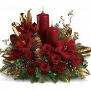 Fiori rossi, foglie d'oro e bacche oro e argento fanno da cornice alla classica candela rossa natalizia.