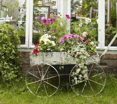 Una veranda in legno e vetro, che fa da sfondo ad una carriola fioriera