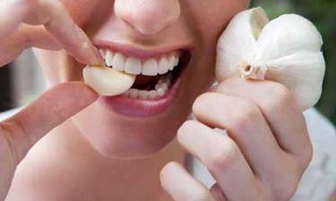 Foto di una ragazza che mangia l'aglio crudo