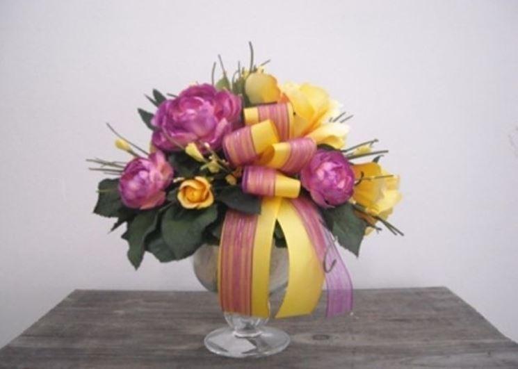 Composizione di vaso con fiori finti e nastrini colorati